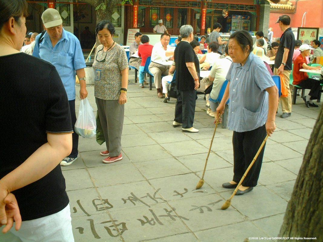 目をつぶって地面に字を書く人
